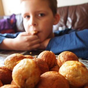 Boy eating a biscuit from a biscuit bowl
